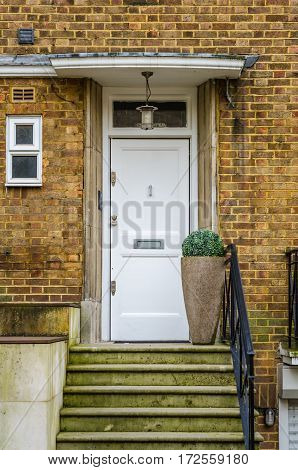 the entrance to a building stone steps on the right side of the metal railing on the left side of a low wall white window peak at the entrance with a stylish lamp a big pot with green plant brick wall