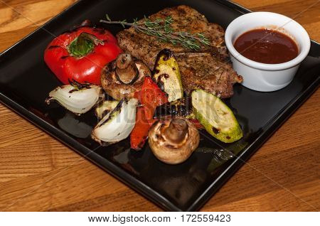 Grilled vegetables with steak on a black plate