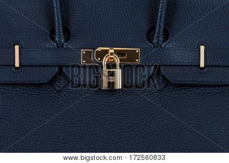 Closeup view of female blue leather handbag with golden clasp. Fashion background.
