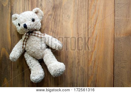 Teddy bear on wooden background with empty copyspace