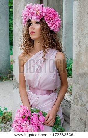 portrait on young beautiful curly woman in the peony wreath outdoor on old ruin background