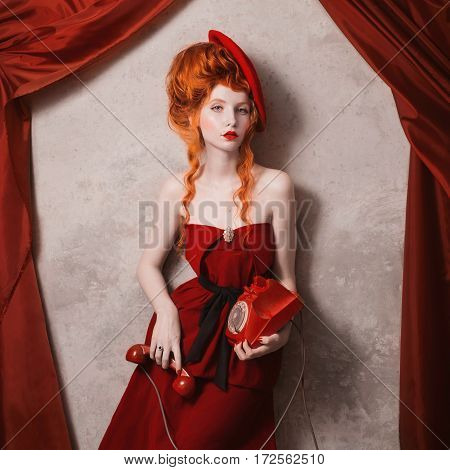 Redhead curly girl in a red beret her lips smeared red lipstick and holding a disk telefon. A woman in a red dress on a gray background. Retro lady. Photo in theater actress. Retro film. Art photo