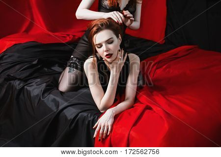 Two red-haired girl hug on the black and red background. Two lesbian women. Long red hair. Beautiful sexy lingerie transparent. Love between girls.