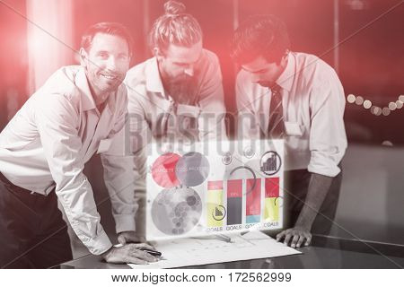 Digital generated image of multi colored graph charts against businessman smiling while colleagues discussing over blueprint