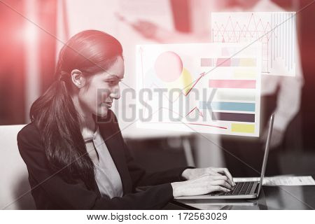 Graph against portrait of businesswoman working on laptop