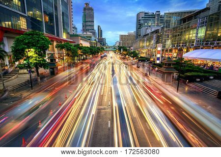 Busy street in the city at dusk full of car light streaks; dynamic blue hour shot with long exposure motion blur effect