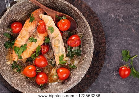 Closeup shot of fried salmon steak with lemon and vegetables on frying pan.