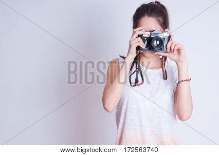 Woman photographer with camera against gray background
