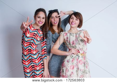 Studio lifestyle portrait of three best friends hipster girls wearing stylish bright dresses, going crazy and having great time together