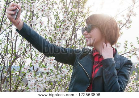 Lifestyle portrait of fashionable woman wearing stylish jacket, checkered shirt, jeans, glasses and taking selfie