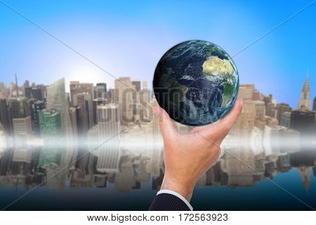 Businessman pointing little earth with his finger against new york