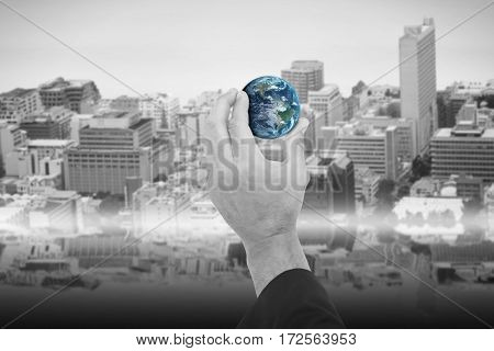 Hand presenting little earth against view of crowded buildings in city