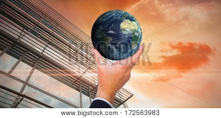 Businessman pointing little earth with his finger against sunrise over magical sea
