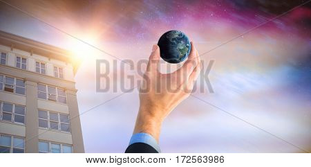 Businessman holding little earth in presentation against aurora night sky in purple