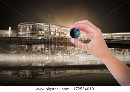 Hand presenting little earth against illuminated modern building