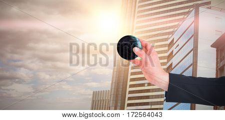 Businessman in suit holding little earth against sky