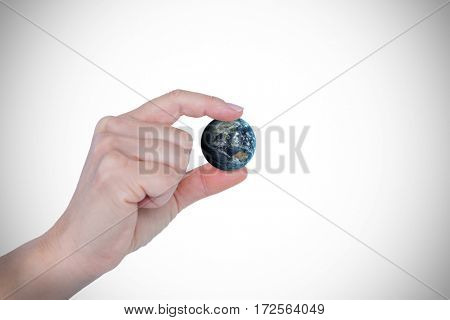Close-up of gesturing hand against image of earth