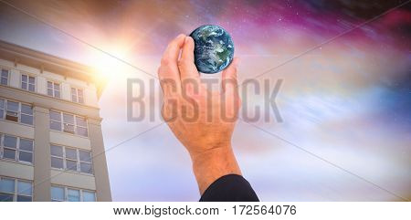 Hand presenting little earth against aurora night sky in purple