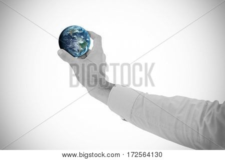 Businessman holding hand out in presentation against globe of earth