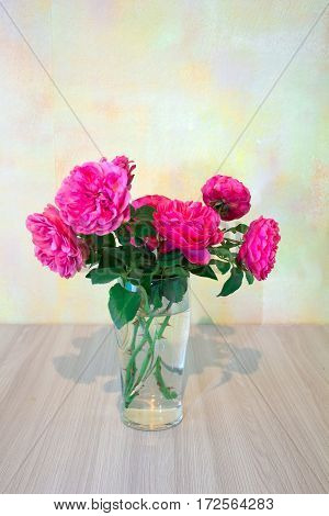 pink roses in a glass vase on a wooden table on a background of pale yellow walls