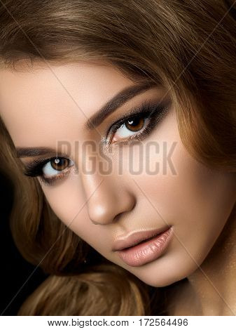 Beauty portrait of young woman with golden makeup. Perfect skin and fashion makeup smokey eyes. Studio shot. Sensuality passion trendy luxurious makeup concept.