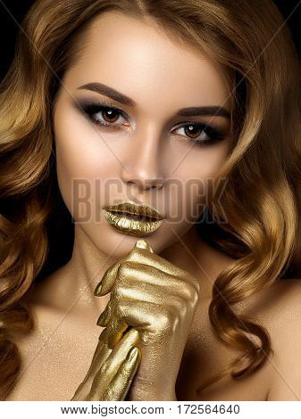 Beauty portrait of young woman with golden makeup. Perfect skin and fashion makeup with gold accents. Smokey eyes. Studio shot. Sensuality passion trendy luxurious makeup concept.