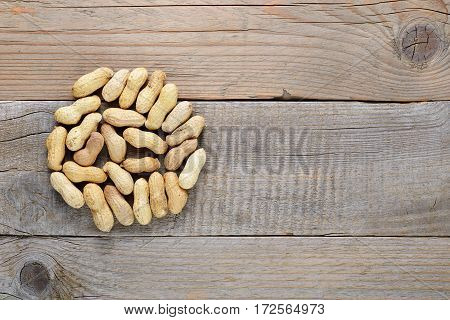 Peanuts on wooden table top view with copy-space