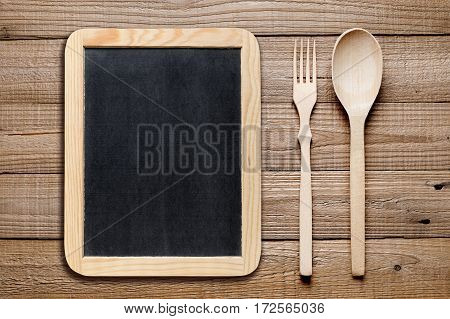Blank blackboard wooden fork and knife on table