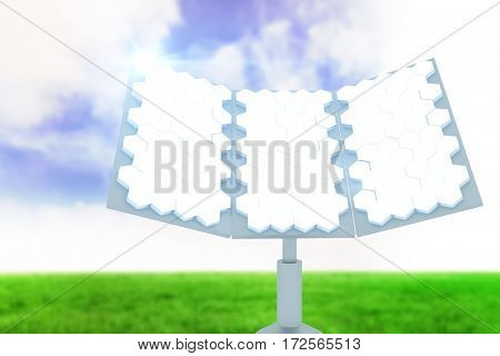 Digitally generated image of hexagon shaped solar panel against blue sky over green field
