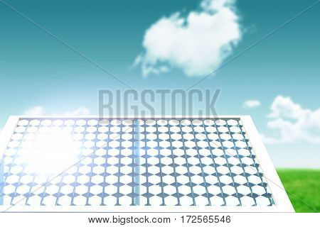 Solar panel with hexagon shape glasses against blue sky over green field
