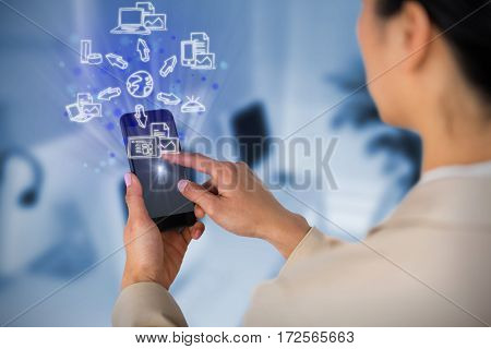 Businesswoman using mobile phone against computers and headsets