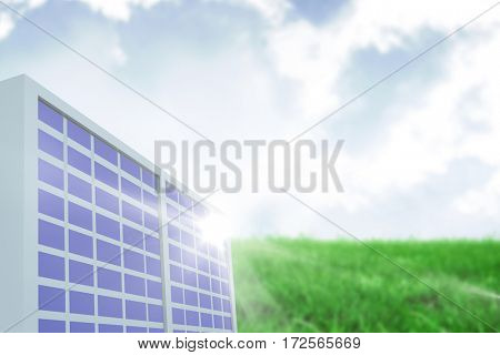 Solar panel against white screen against sky over green field