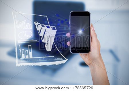 Hand holding mobile phone against white background against laptop on desk with mug of coffee and glasses