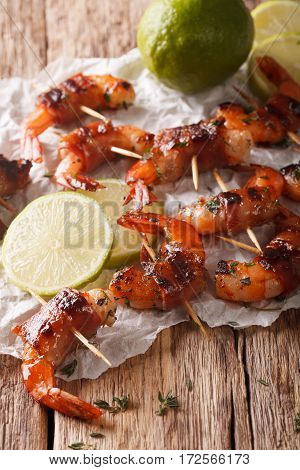 Tiger Prawns Wrapped In Bacon On Skewers With Thyme And Lime Close Up. Vertical