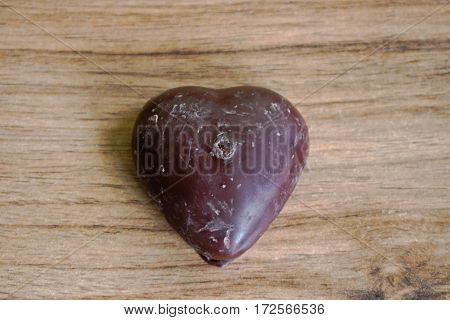 Chocolate covered gingerbread heart on a wooden table