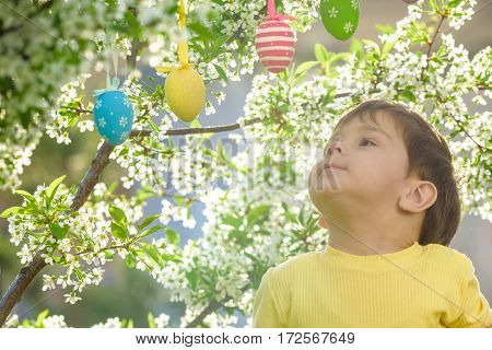 little kid boy in Easter hunting eggs in spring garden outdoors. On warm sunny day with blooming trees on background.