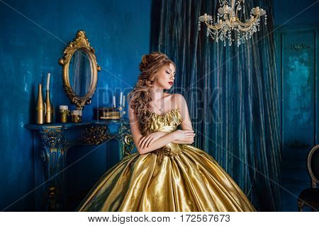 Beautiful woman in a golden ball gown in the great blue interior