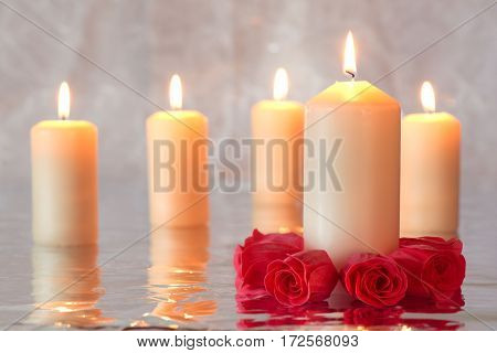 Group of burning candles with reflection and a group of red roses surrounding the candle in the foreground
