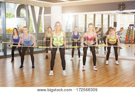 Deadlift with light weight. Group of young women in fitness class making exercises. Girls do squats with barbells. Healthy lifestyle in fitness club