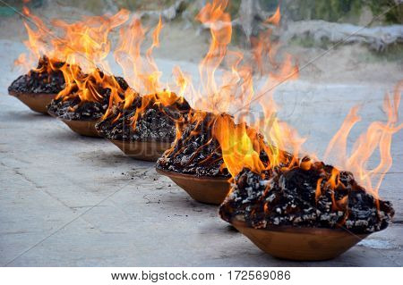 Close up view of a fire puja in the brown clay bowls near the temple