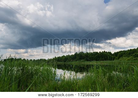 Green countryside lake landscape with blue cloudy sky background