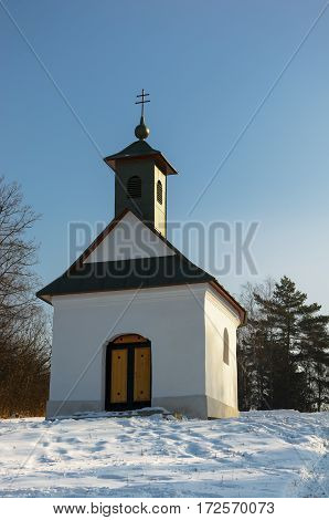 Little chapel in snowy landscape during cold winter days. Chapel is shortly after reconstruction