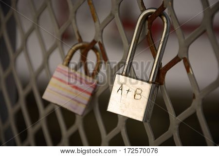 Detail of padlock locked on mesh. Heart A+B wrote on padlock