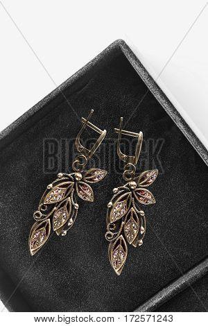 Vintage gold earrings in black jewel box closeup