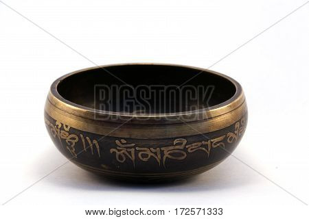 Tibetan singing bowl engraved with the mantra side view on white background