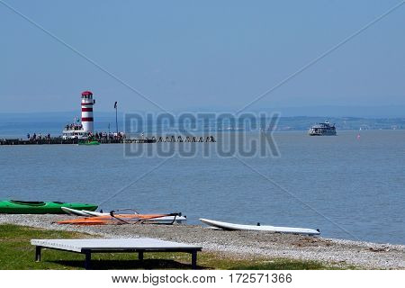 Perspective of the beach at Lake Neusiedl with lighthouse and tourists - austria
