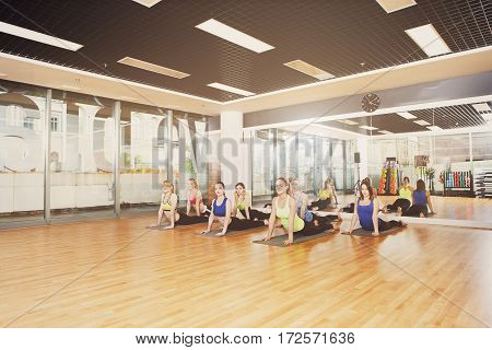 Group of young women in fitness center making exercises on sunny morning. Girls do back stretching. Healthy lifestyle, gymnastics or yoga studio