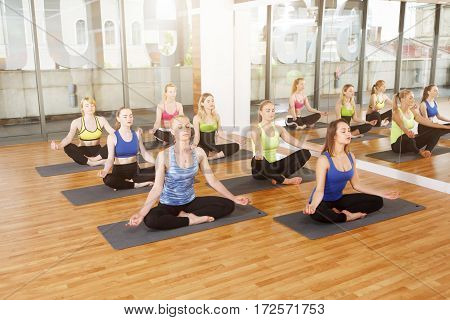 Girls do meditation pose for relaxation. Group of young women in yoga class making exercises. Healthy lifestyle in fitness center