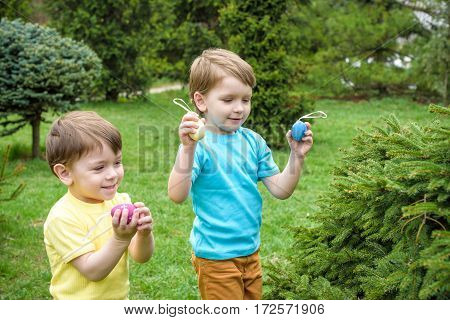 Kids On Easter Egg Hunt In Blooming Spring Garden. Children Searching For Colorful Eggs In Flower Me