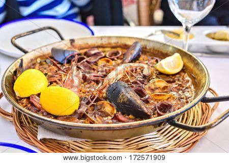 Tasty Seafood Paella in black pan -traditional spanish rice dish meal
